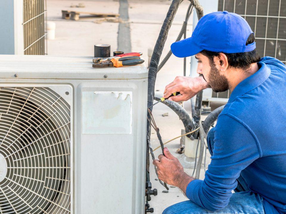 man performing maintenance on HVAC unit during Home Watch visit
